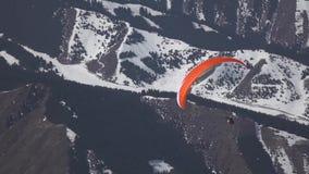 Vuelo de un turista en un ala flexible contra el contexto de montañas hermosas almacen de metraje de vídeo