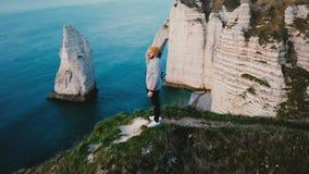 Vuelo del abejón alrededor del hombre de negocios emocionado feliz joven que mira vista al mar épica encima del acantilado rocoso metrajes