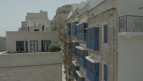 Vuelo del abejón detrás a través de la calle vieja hermosa, La Valeta, Malta Viejo, ventanas del vintage, balcones - 4K almacen de video