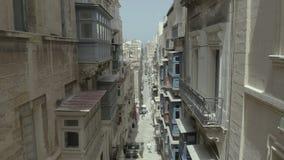 Vuelo del abejón detrás a través de la calle vieja hermosa, La Valeta, Malta Viejo, ventanas del vintage, balcones - 4K metrajes