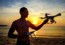 Vuelo del abejón en la puesta del sol sobre el mar Hombre que aterriza el frome del abejón el aire Frome de la foto de la puest fotografía de archivo libre de regalías