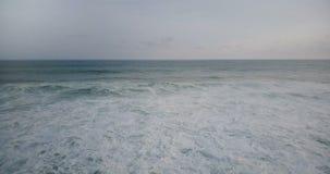 Vuelo del abejón hacia la ola oceánica espumosa blanca grande que alcanza la orilla y estrellarse, creando textura natural del ag metrajes