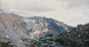 Vuelo del abejón sobre el pico cubierto de piedra hermoso que revela el canto masivo de la montaña en el parque nacional los E.E. metrajes