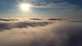 Vuelo del abejón sobre las nubes con un sol hermoso metrajes