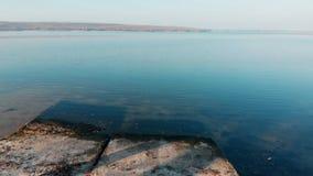 Vuelo del abejón sobre las placas de piedra y lanzamiento sobre el río azul Despegue ascendente escénico sobre el lago Viaje y el almacen de metraje de vídeo
