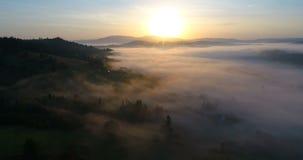 Vuelo del abejón sobre pueblo de montaña de niebla soñador durante salida del sol almacen de metraje de vídeo