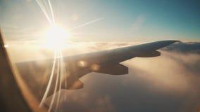 Vuelo del aeroplano Ala de un vuelo del aeroplano sobre las nubes con el cielo de la puesta del sol metrajes