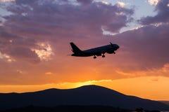 Vuelo del aeroplano del pasajero en el cielo en la puesta del sol fotos de archivo