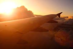 Vuelo del aeroplano sobre las nubes en la puesta del sol imagenes de archivo