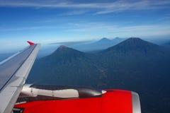 Vuelo del ala del aeroplano sobre las montañas foto de archivo