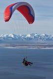 Vuelo del ala flexible en el fondo de la montaña y del mar Imagenes de archivo