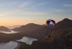 Vuelo del ala flexible en la puesta del sol en Oludeniz, Turquía foto de archivo libre de regalías