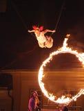 Vuelo del artista del circo a través del cicle del fuego Imágenes de archivo libres de regalías