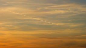 Vuelo del avión de pasajeros del aeroplano del jet que deja el rastro del vapor a través del cielo, de las nubes y del sol en la  almacen de video