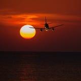 Vuelo del avión de pasajeros en una baja altitud en la puesta del sol y el sol b Imagen de archivo libre de regalías