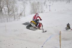 Vuelo del corredor del Snowmobile abajo de la montaña Imagenes de archivo