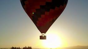 Vuelo del globo del aire caliente delante del sol almacen de video