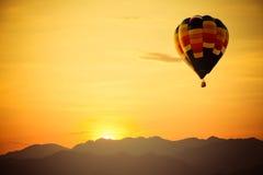 Vuelo del globo del aire caliente sobre la montaña con puesta del sol Foto de archivo libre de regalías