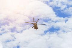 Vuelo del helicóptero en el cielo azul con el fondo mullido blanco hermoso de las nubes fotos de archivo