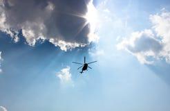 Vuelo del helicóptero en el cielo entre los rayos del sol Imagen de archivo libre de regalías