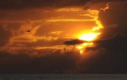 Vuelo del helicóptero en la puesta del sol Fotografía de archivo