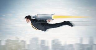 Vuelo del hombre de negocios del super héroe con el cohete del paquete del jet sobre el CIT Imagen de archivo libre de regalías