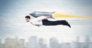 Vuelo del hombre de negocios del super héroe con el cohete del paquete del jet sobre el CIT Foto de archivo libre de regalías