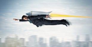 Vuelo del hombre de negocios del super héroe con el cohete del paquete del jet sobre el CIT Foto de archivo