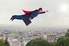 Vuelo del hombre de negocios del super héroe sobre una ciudad Foto de archivo libre de regalías