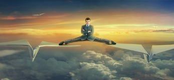 Vuelo del hombre de negocios en los aviones de papel Foto de archivo