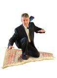 Vuelo del hombre de negocios en una alfombra mágica Imágenes de archivo libres de regalías