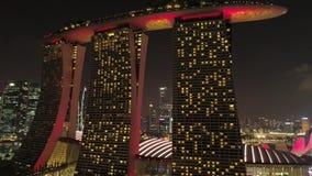 Vuelo del horizonte de Singapur de la vista nocturna sobre Marina Bay Sands Hotel tiro Vistas a?reas del horizonte de Singapur en metrajes