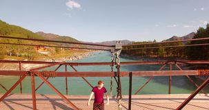 vuelo del Mediados de-aire sobre el turista del hombre joven que permanece a través de puente colgante almacen de metraje de vídeo