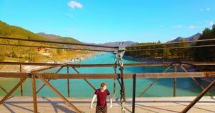 vuelo del Mediados de-aire sobre el turista del hombre joven que permanece a través de puente colgante metrajes