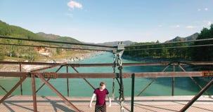 vuelo del Mediados de-aire sobre el turista del hombre joven que permanece a través de puente colgante almacen de video