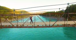vuelo del Mediados de-aire sobre paseo turístico del hombre joven a través de puente colgante almacen de video