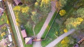 Vuelo del movimiento vertical sobre hombre en el jardín sirva los controles un abejón cerca de un edificio gris en un césped verd almacen de video