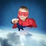 Vuelo del niño del super héroe sobre las nubes Fotografía de archivo