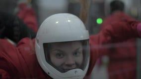 Vuelo del skydiver de la mujer joven del retrato en túnel de viento El lanzarse en paracaídas y el saltar en caída libre almacen de metraje de vídeo