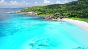 vuelo delantero del abejón 4K sobre el agua cristalina del océano de la turquesa cerca a la playa tropical del paraíso con la  almacen de metraje de vídeo