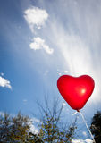 Vuelo en forma de corazón rojo del globo en cielo Imágenes de archivo libres de regalías