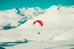 Vuelo en tándem del ala flexible sobre Gudauri Paracaídas colorido Forma de vida activa, aficiones extremas El Paragliding, explo Imagenes de archivo