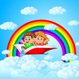 Vuelo feliz de los niños en el libro abierto grande con el fondo del arco iris y de la nube ilustración del vector