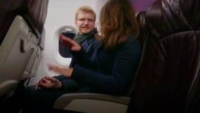 Vuelo feliz del hombre joven y de la mujer en el avión con la comodidad, manos de la tenencia, hablando metrajes