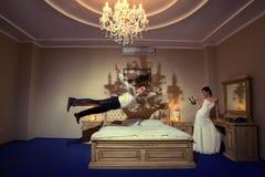 Vuelo feliz del novio en cama Fotos de archivo libres de regalías