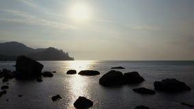 Vuelo hacia las montañas sobre ondas en el Mar Negro que hace frente a la salida del sol Vista aérea de montañas, de rocas, de pi almacen de metraje de vídeo