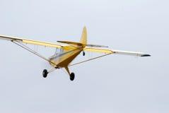 Vuelo inferior del aeroplano amarillo del monomotor Foto de archivo libre de regalías