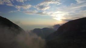 Vuelo a la puesta del sol entre las montañas almacen de metraje de vídeo