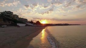 Vuelo a lo largo de la costa en pequeña ciudad, opinión del abejón de la salida del sol Nea Kallikratia, Grecia almacen de metraje de vídeo