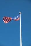 Vuelo malasio de la bandera nacional en viento en un polo con el cielo azul Fotos de archivo libres de regalías
